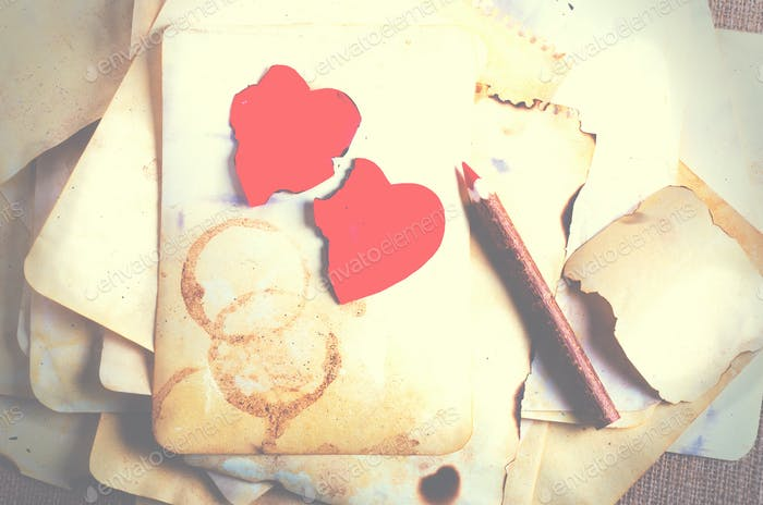 Stack old papers, notebook, wooden pencil and two vintage red hearts on burlap, sackcloth background