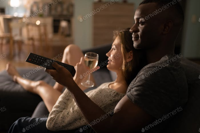 Multiethnic couple with wineglass watching TV