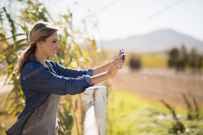 Woman taking selfie on mobile phone in park