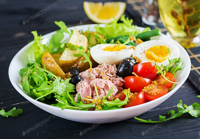 Healthy hearty salad of tuna, green beans, tomatoes, eggs, potatoes, black olives close-up