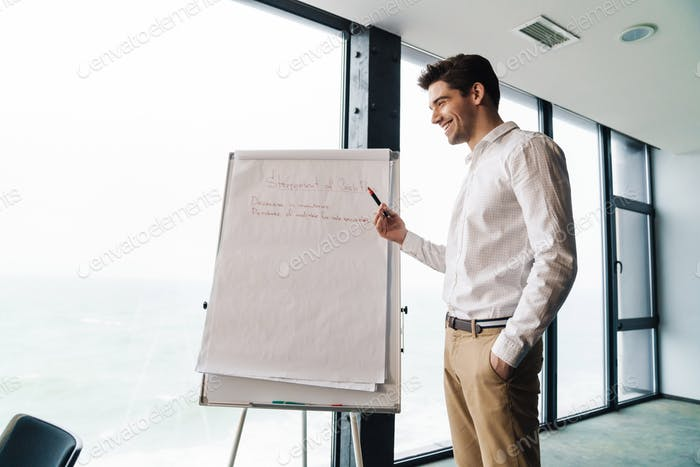 Portrait of businessman standing by flipchart while working in office