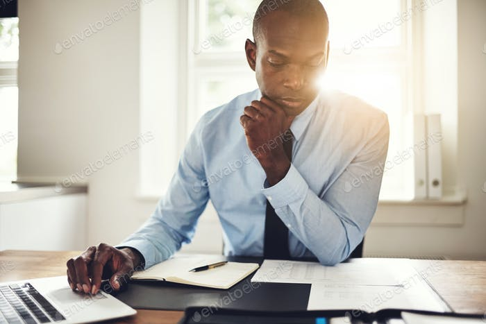 Young executive reading paperwork and using a laptop
