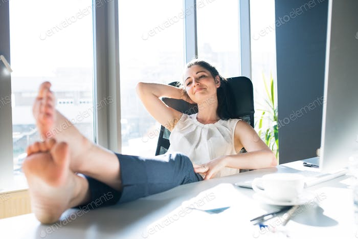 Businesswoman in her office sitting with legs on desk.