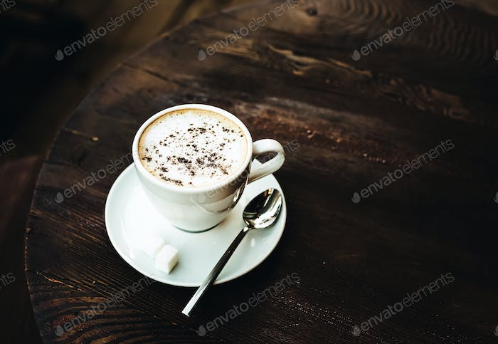 Cup of cappuccino on old dark wooden table, toned