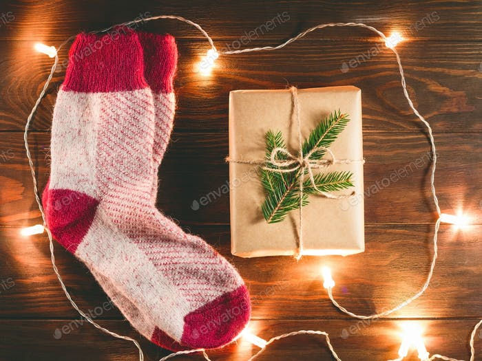 Top view on woollen socks and gift box with festoon lights on a wooden background