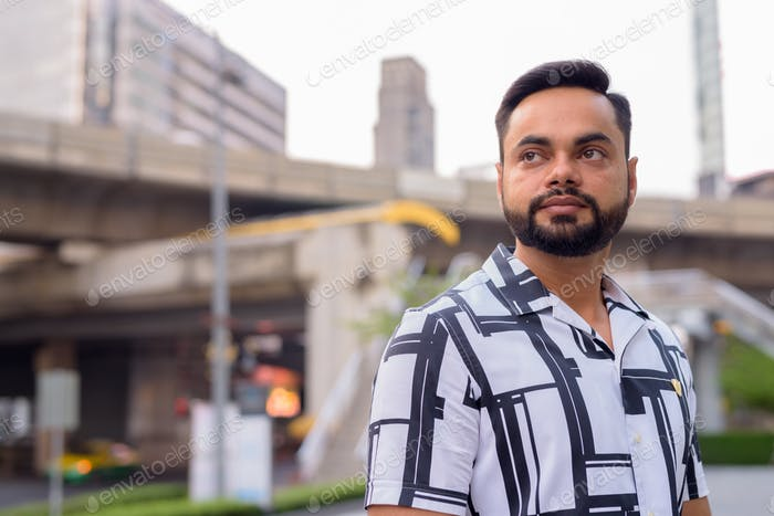 Face of young bearded Indian man thinking against view of the skytrain station outdoors
