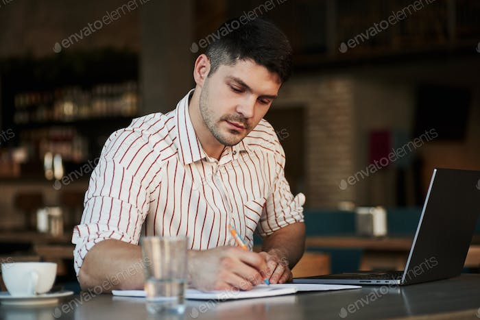 Useful notes. Adult man sits in cafe at daytime and using the laptop for the remote work