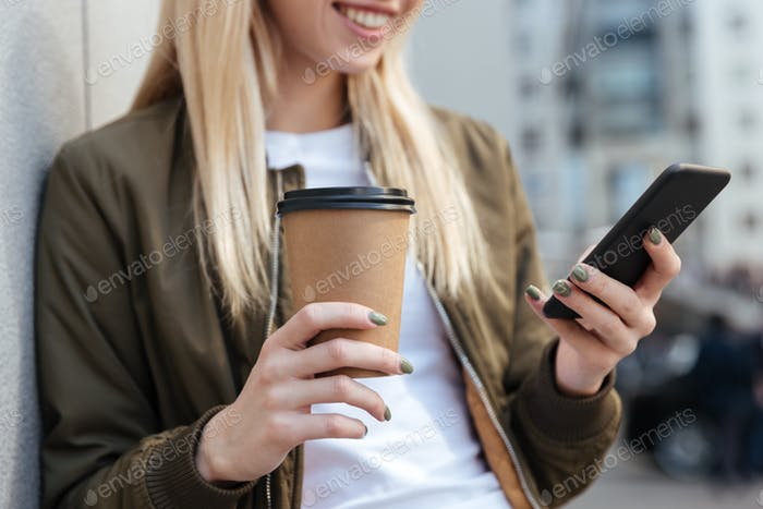 Cropped image of blonde woman using smartphone
