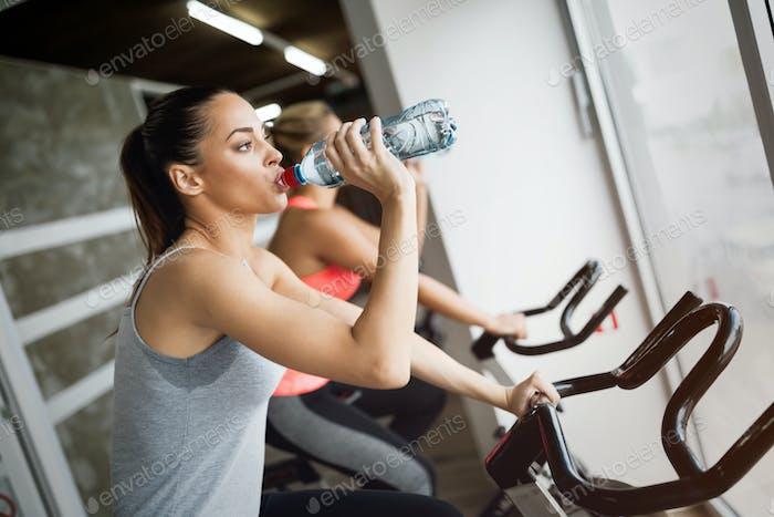 Beautiful woman riding sport bike in gym