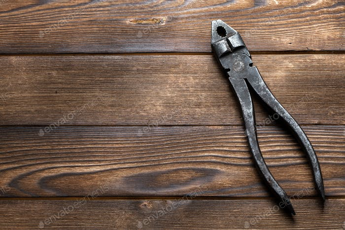 old rusty pliers on wooden background