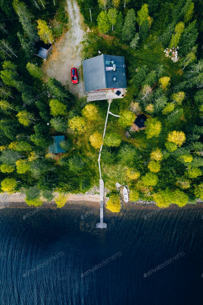 Aerial top view of log cabin or cottage with red car in spring forest in rural Finland