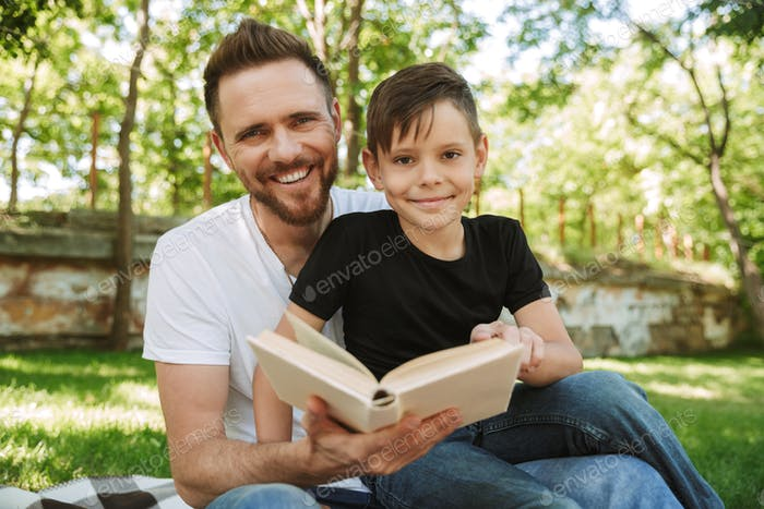 Father sitting with his little son outdoors reading book.