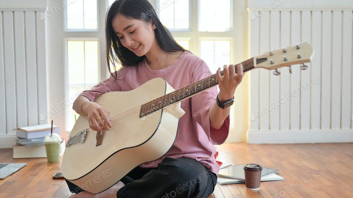 Teenage girl playing a guitar while staying at home while quarantine the Covid-19 virus.