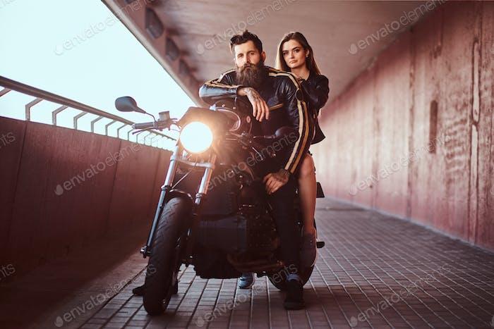 Brutal bärtiger Biker in schwarzer Lederjacke und sinnlich brünettes Mädchen
