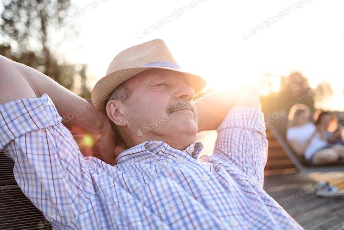 Alter hispanischer Mann sitzt auf der Bank, lächelnd, genießen sommerlichen sonnigen Tag.