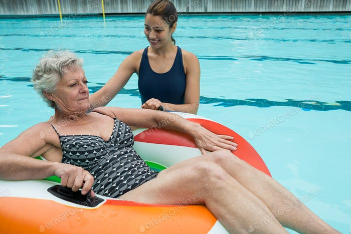 Trainer assisting senior woman on inflatable ring