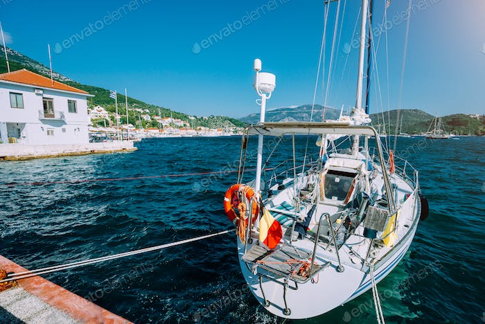 Sailing boat moored up in the picturesque Greek town. Mediterranean landscape of green hills