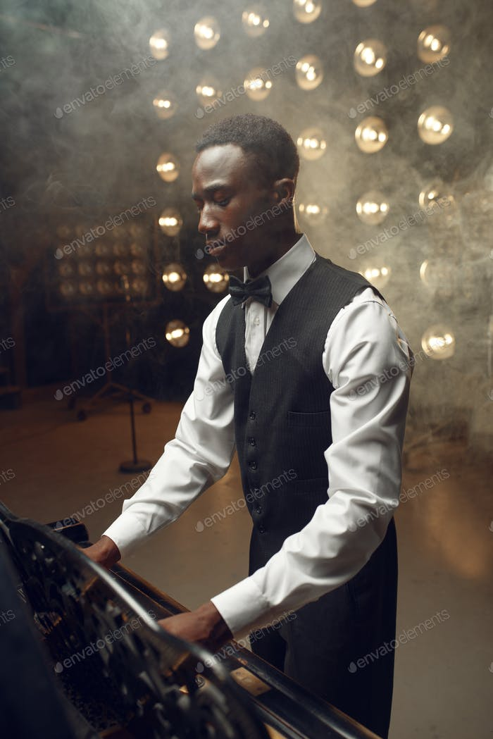 Black grand piano player playing on the stage