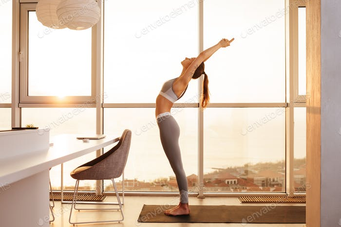 Young lady in sporty top and leggings standing practicing yoga at home over beautiful window