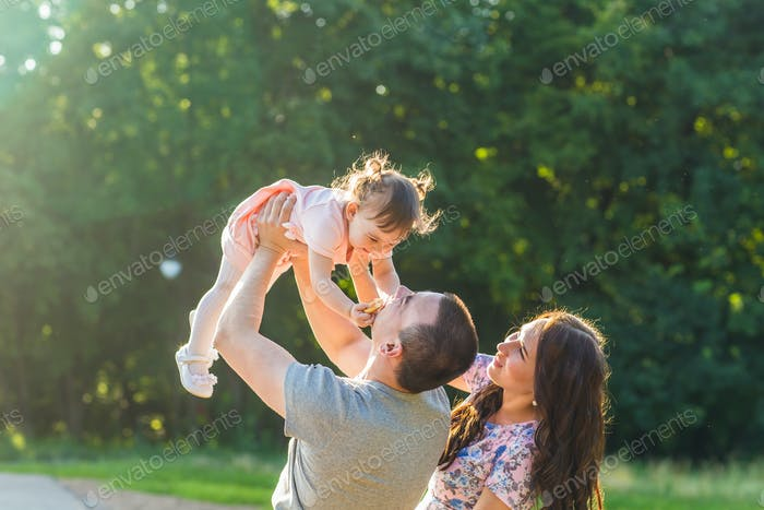 happy family concept - father, mother and child daughter having fun and playing in nature.