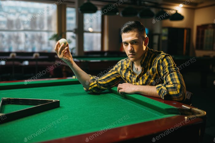 Male billiard player holds white ball at the table