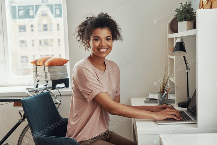 Beautiful young African woman using laptop and smiling while spending time at home
