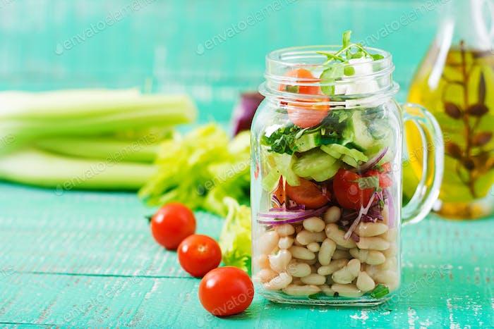 Salat aus weißen Bohnen, Tomaten, Sellerie, Gurken, Rucola, roten Zwiebeln und Feta-Käse in einem Glas.