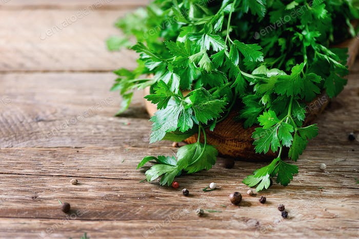 Bunch of fresh organic parsley on wooden background with copyspace, rustic and vintage style