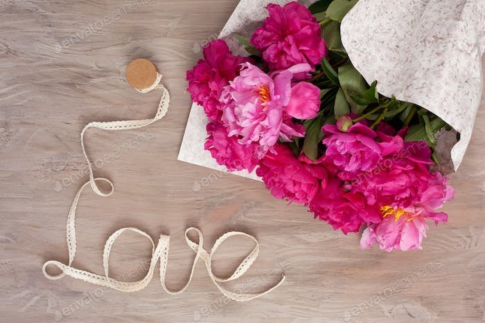 Ribbon formed in word Love with peonies. Concept of love, celebration, wedding, saint valentine