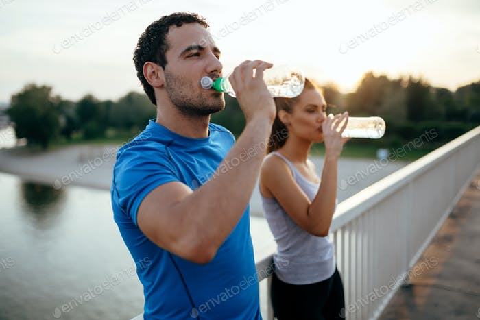 Athletic couple drinking water
