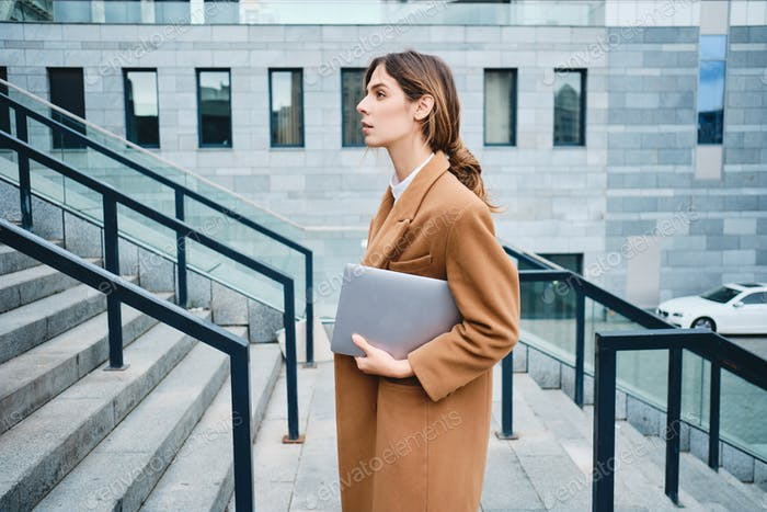 Side view of young gorgeous businesswoman in coat with laptop confidently looking aside outdoor