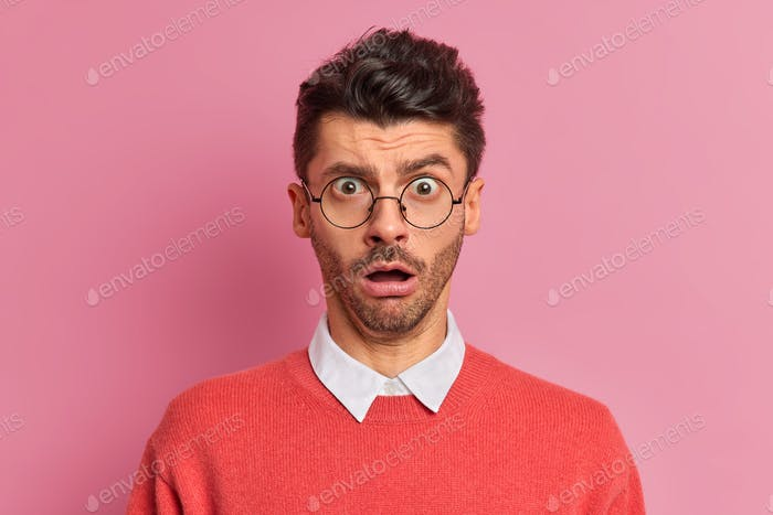 Close up shot of amazed shocked man holds breath from shock stares through optical glasses opens mou