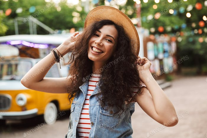 Photo of happy european woman 18-20 with curly brown hair, laugh