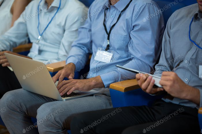 Business executives participating in a business meeting using electronic devices