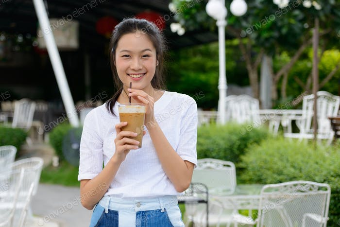 Happy young beautiful Asian woman drinking coffee at the coffee shop outdoors