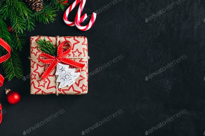Christmas background with fir branches and a gift box with a red bow on a dark concrete background.
