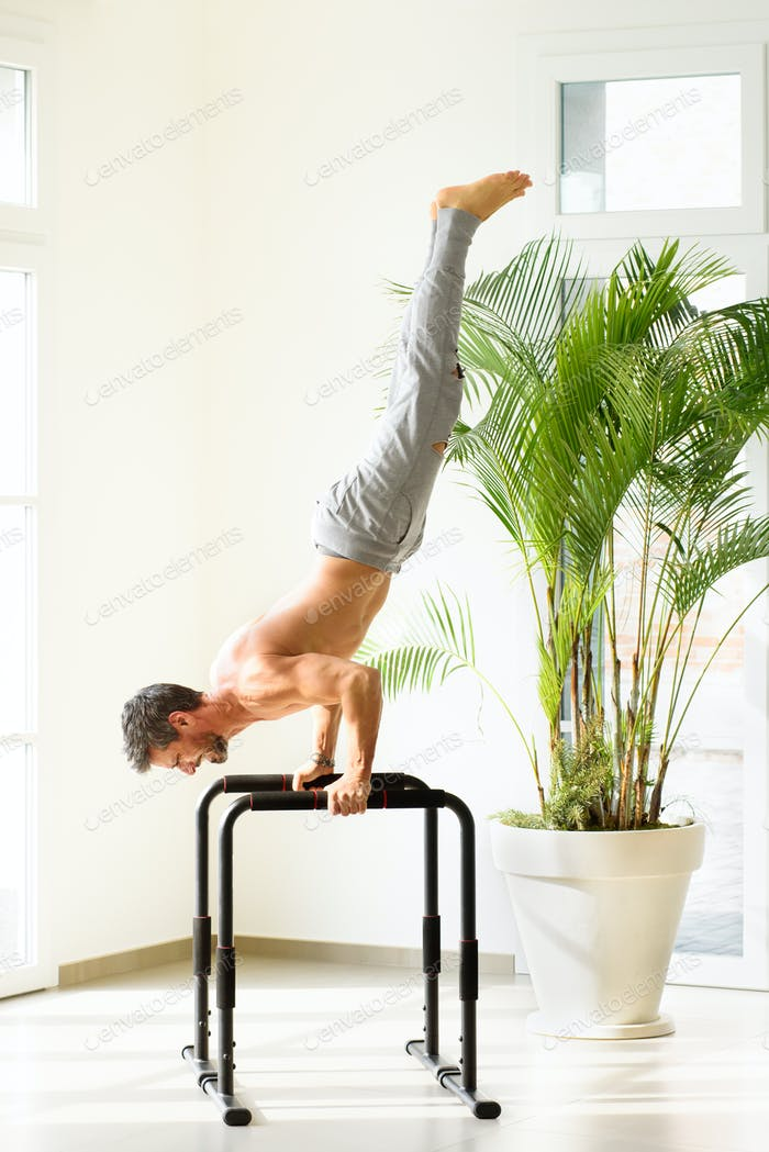 Muscular man doing handstand push ups