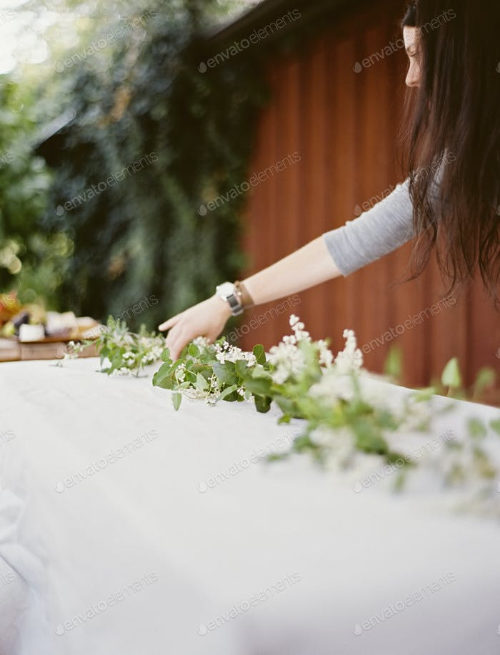 A woman laying a table outside.