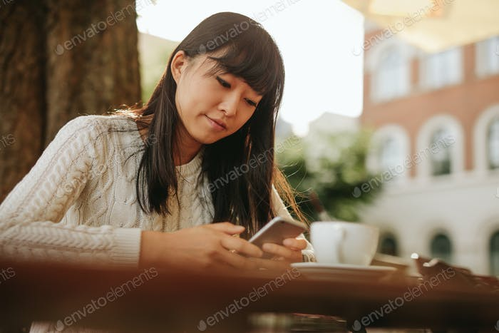 Young woman with a coffee using mobile phone