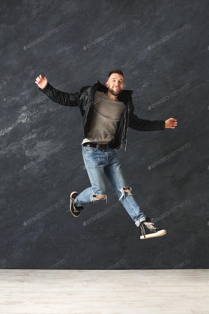 Happy handsome man jumping in studio