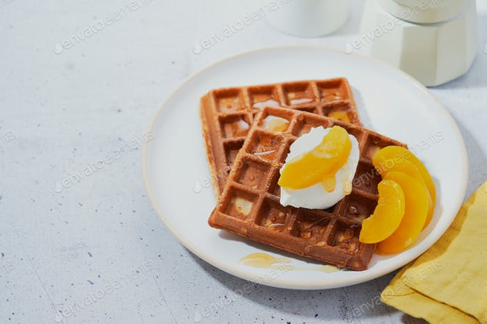 Belgian Waffle with honey, peaches in syrup, whipped cream.