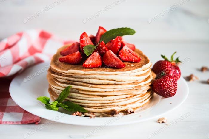 Köstliche Pfannkuchen mit Erdbeere auf Holzhintergrund