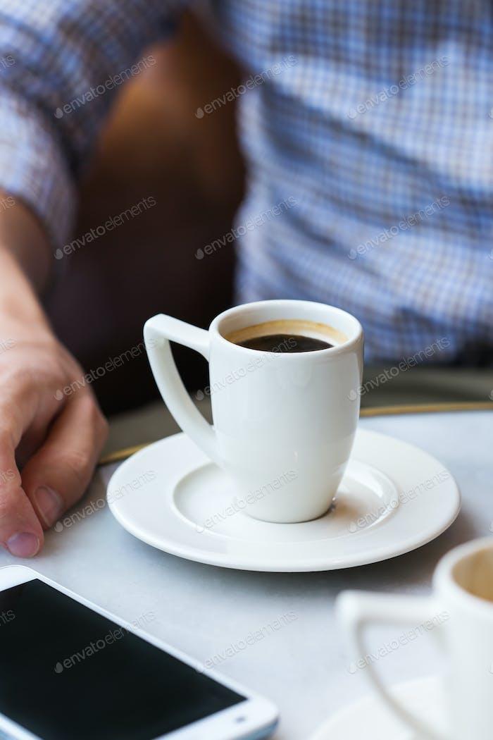 Geschäftsmann sitzt im Café, trinkt Morgenkaffee und mit dem Smartphone