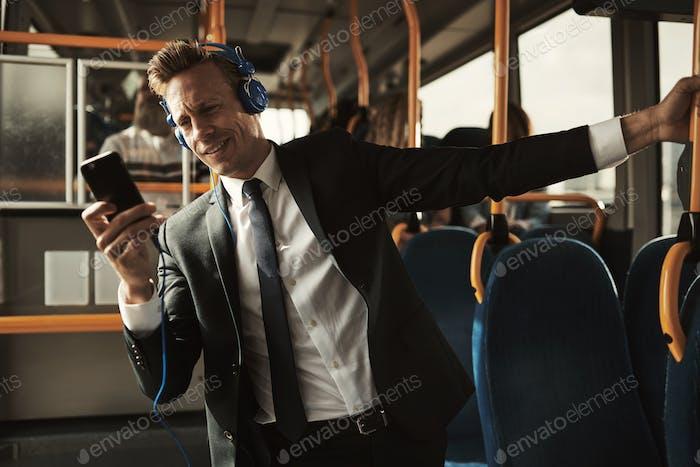 Улыбающийся бизнесмен, стоящий на автобусе, слушая музыку