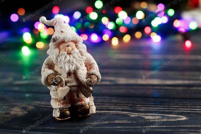 christmas santa claus toy on background of colorful garland lights
