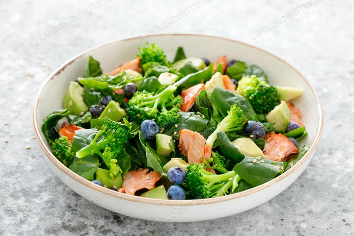Salmon fish and avocado salad with fresh spinach leaves, broccoli, blueberry dressed with olive oil