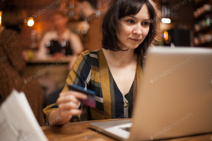 Pretty young woman holding credit card and looking at laptop in a vintage pub