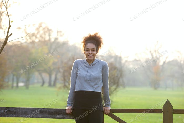 Happy natural young woman standing outdoors