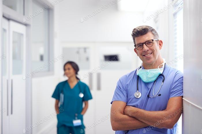Porträt von Reifen Männlich Arzt tragen Peelings stehend in beschäftigt Krankenhaus Korridor
