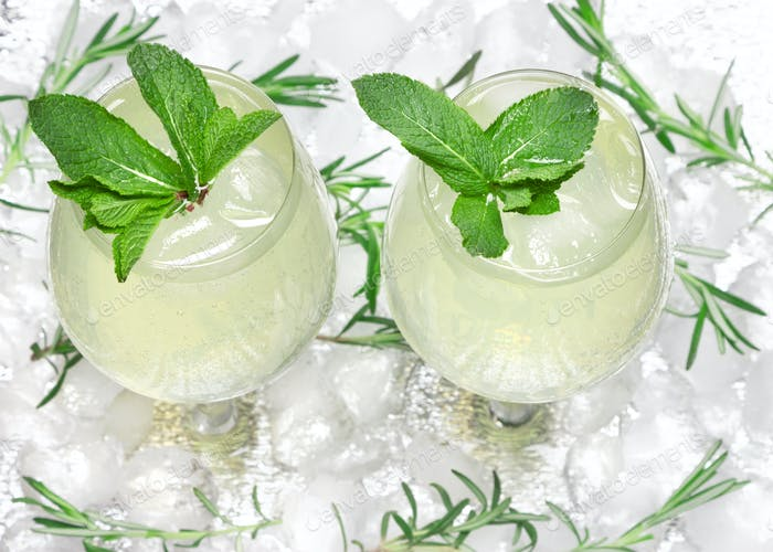 Chilled drink with mint in glass goblets on ice cubes